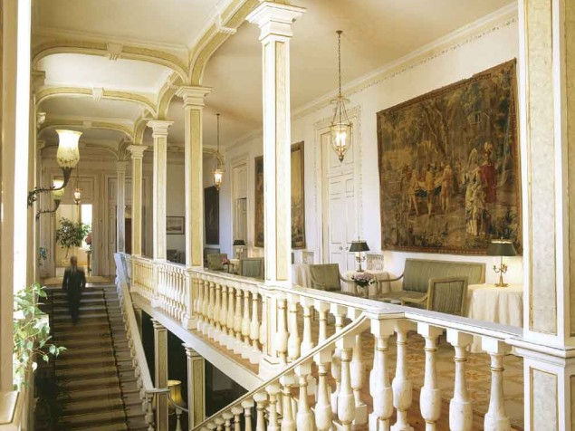 The palace's great ceiling heights enhance the monumental stairs and upper gallery