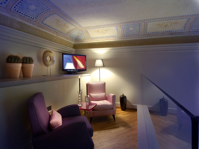 The upper sitting area of a suite is enhanced by the delicate, restored frescoed ceiling