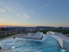 A dramatic rooftop hot bath provides distant views of historic Zurich