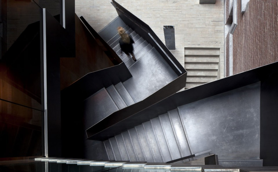 This heavy metal stair offers a bold interplay between the modern world of steel and glass and the warm historic elements of Conservatorium Hotel